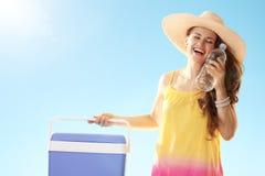 Mujer con la caja más fresca plástica azul que goza de la botella de agua imagen de archivo