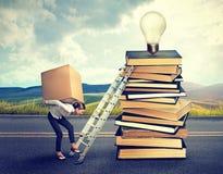 Mujer con la caja pesada que sube las escaleras a la pila superior de libros Fotos de archivo libres de regalías
