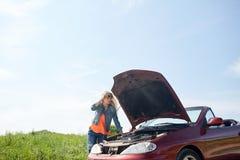 Mujer con la capilla abierta del coche quebrado en el campo Fotos de archivo libres de regalías