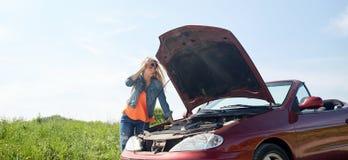 Mujer con la capilla abierta del coche quebrado en el campo Imagenes de archivo