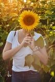 Mujer con la cara cubierta con el girasol imagen de archivo