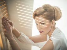 Mujer con la cara interesada con el espía que va del maquillaje a través de la persiana foto de archivo libre de regalías