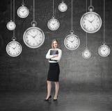 Mujer con la carpeta y muchos relojes Fotografía de archivo