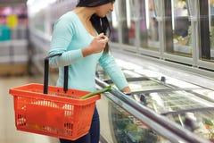 Mujer con la cesta de la comida en el congelador del colmado fotos de archivo libres de regalías