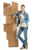 Mujer con la cinta adhesiva que se inclina en las cajas de cartón apiladas imagen de archivo