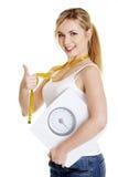 Mujer con la cinta de la báscula de baño y de la medición Foto de archivo libre de regalías
