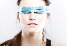 Mujer con la cinta métrica que la cubre ojos Imágenes de archivo libres de regalías