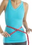 Mujer con la cinta métrica que mide su cintura Imagen de archivo libre de regalías