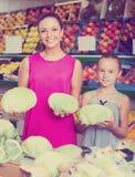 Mujer con la col de compra de la hija en mercado Fotografía de archivo libre de regalías