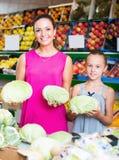 Mujer con la col de compra de la hija en mercado Fotos de archivo libres de regalías