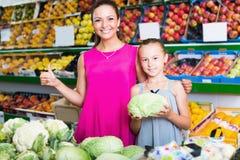 Mujer con la col de compra de la muchacha en la sección de las verduras Foto de archivo libre de regalías