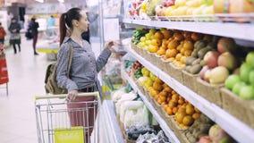 Mujer con la comida en carro de la compra en el colmado metrajes