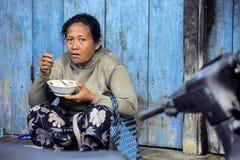 Mujer con la comida en el pueblo Toyopakeh, Nusa del mercado Penida 17 de junio Indonesia 2015 Imagen de archivo libre de regalías