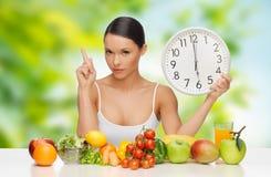 Mujer con la comida y el reloj que muestran seis Foto de archivo