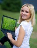 Mujer con la computadora portátil afuera Imágenes de archivo libres de regalías