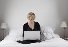Mujer con la computadora portátil en cama Fotos de archivo libres de regalías