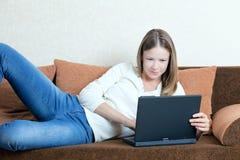Mujer con la computadora portátil en el sofá Fotos de archivo