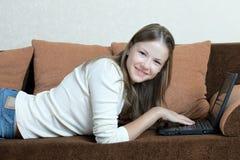 Mujer con la computadora portátil en el sofá Foto de archivo libre de regalías