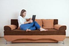 Mujer con la computadora portátil en el sofá imagen de archivo libre de regalías