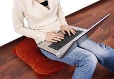 Mujer con la computadora portátil en el suelo Imagen de archivo
