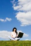 Mujer con la computadora portátil en la hierba verde Imagen de archivo
