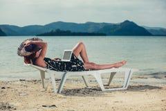 Mujer con la computadora portátil en la playa Fotografía de archivo libre de regalías