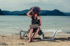 Mujer con la computadora portátil en la playa Fotografía de archivo