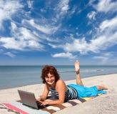 Mujer con la computadora portátil en la playa del mar Foto de archivo libre de regalías