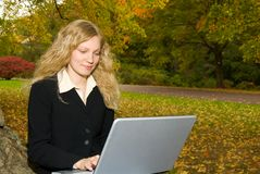 Mujer con la computadora portátil en parque. Imagen de archivo
