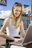 Mujer con la computadora portátil en un cerco urbano de alta tecnología Fotos de archivo