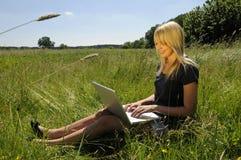 Mujer con la computadora portátil en un prado Imagen de archivo