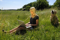 Mujer con la computadora portátil en un prado Fotos de archivo libres de regalías