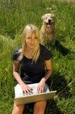 Mujer con la computadora portátil en un prado Imagen de archivo libre de regalías