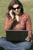 Mujer con la computadora portátil que habla en el teléfono móvil Fotos de archivo