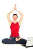 Mujer con la computadora portátil que hace yoga Fotos de archivo libres de regalías