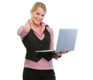 Mujer con la computadora portátil que muestra los pulgares para arriba Fotografía de archivo libre de regalías