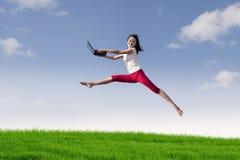 Mujer con la computadora portátil que salta en prado Imagenes de archivo