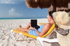 Mujer con la computadora portátil que se relaja en el deckchair imagenes de archivo