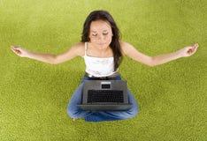 Mujer con la computadora portátil que se relaja en la alfombra verde Imágenes de archivo libres de regalías
