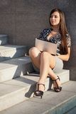 Mujer con la computadora portátil que se sienta en las escaleras Imagenes de archivo