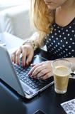 Mujer con la computadora portátil y el café Foto de archivo libre de regalías