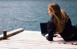 Mujer con la computadora portátil y el mar Fotografía de archivo libre de regalías