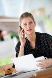 Mujer con la computadora portátil y el teléfono imagen de archivo libre de regalías