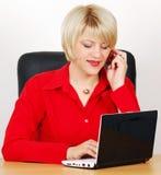 Mujer con la computadora portátil y el teléfono Imagen de archivo