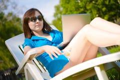 Mujer con la computadora portátil y el vidrio de martini al aire libre Fotos de archivo