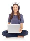 Mujer con la computadora portátil y los auriculares Fotos de archivo libres de regalías
