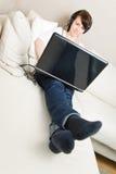Mujer con la computadora portátil y los auriculares Fotografía de archivo libre de regalías