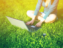 Mujer con la computadora portátil y móvil en parque Imagen de archivo libre de regalías