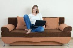 Mujer con la computadora portátil en el sofá Fotografía de archivo