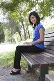 Mujer con la computadora portátil en parque Imagen de archivo